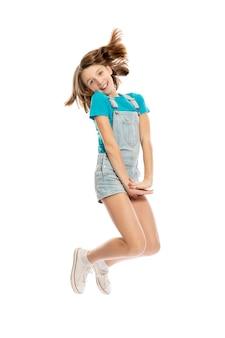 Adolescente en salopette en jean dans une pose volante, pleine hauteur. isolé sur fond blanc