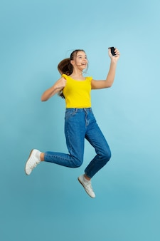 Adolescente sautant haut avec smartphone
