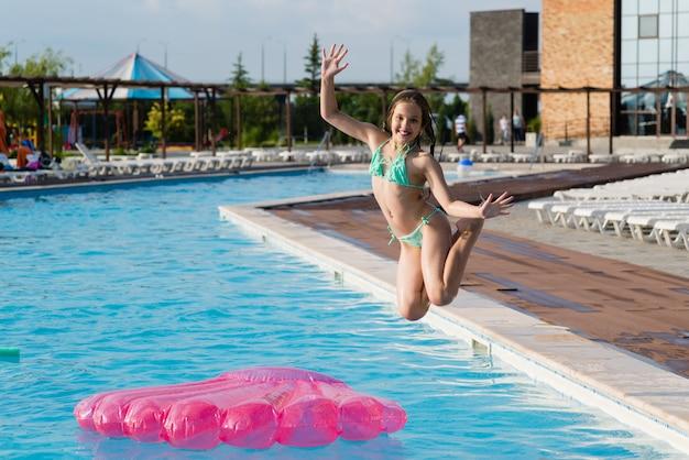 Adolescente saute dans la piscine