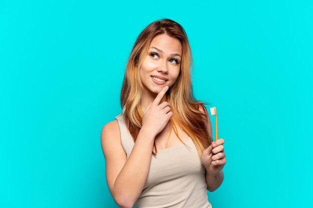Adolescente se brosser les dents sur fond bleu isolé en levant tout en souriant