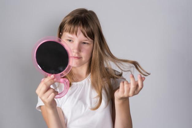 Une adolescente se regarde dans un miroir et regarde un bouton