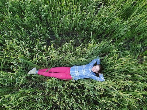 Une adolescente se trouve dans l'herbe verte au coucher du soleil, vue de dessus, marche et unité avec la nature