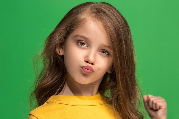 Adolescente sérieuse, triste, douteuse et réfléchie debout au studio vert. émotions humaines, concept d'expression faciale