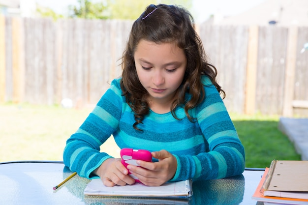 Adolescente avec smartphone à faire leurs devoirs