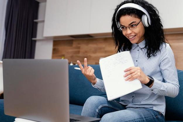 Adolescente smiley avec des écouteurs pendant l'école en ligne