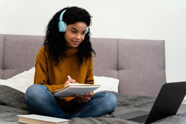 Adolescente smiley utilisant un ordinateur portable pour l'école en ligne