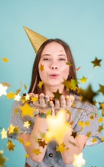 Adolescente soufflant des confettis