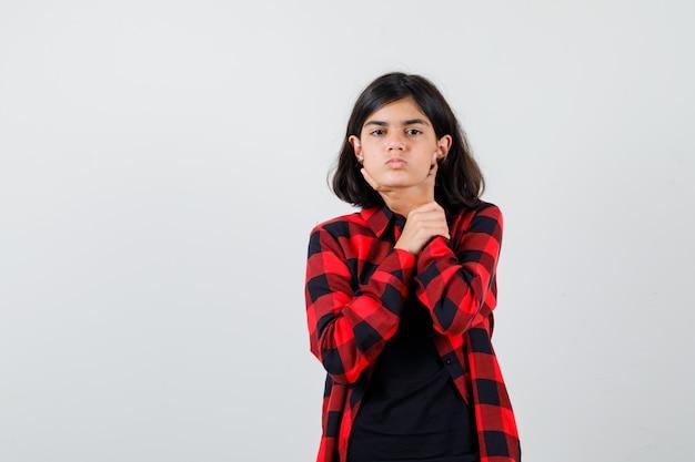 Adolescente souffrant de maux de gorge en t-shirt, chemise à carreaux et ayant l'air malade. vue de face.
