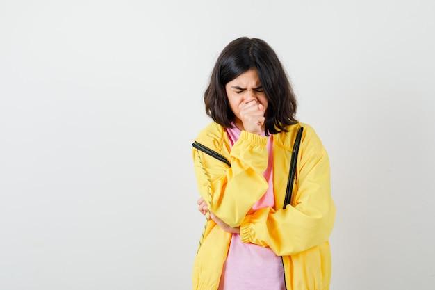 Adolescente souffrant de toux en t-shirt, veste jaune et semblant douloureuse, vue de face.