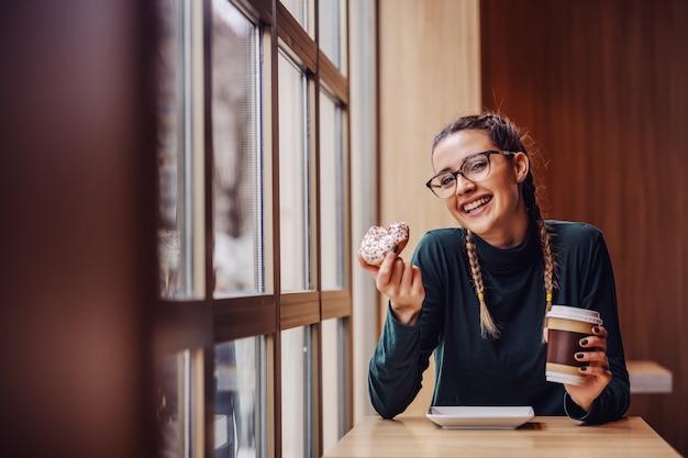 Adolescente souriante assise dans un café, tenant un beignet et une tasse jetable avec du café pendant la pause entre les cours.