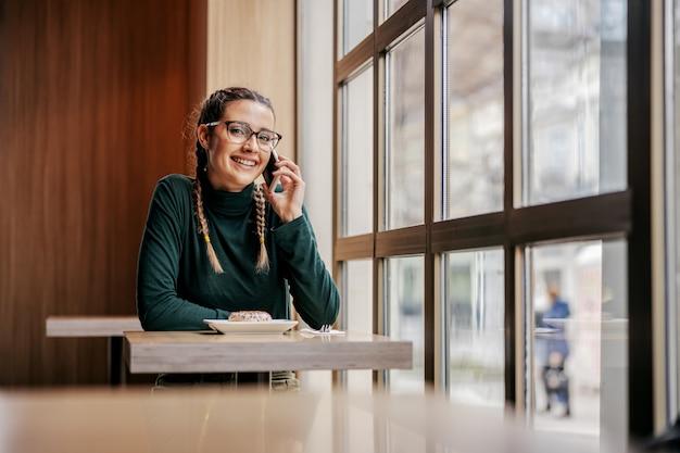 Adolescente souriante assise dans la cafétéria à côté de la fenêtre et avoir une conversation téléphonique. concept mondial de télécommunication.