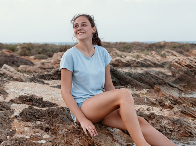 Adolescente souriante assise sur une falaise au bord de la mer avec les jambes dans l'eau au coucher du soleil et levant les yeux, vêtue d'un t-shirt bleu et d'un short en jean. maquette de t-shirt