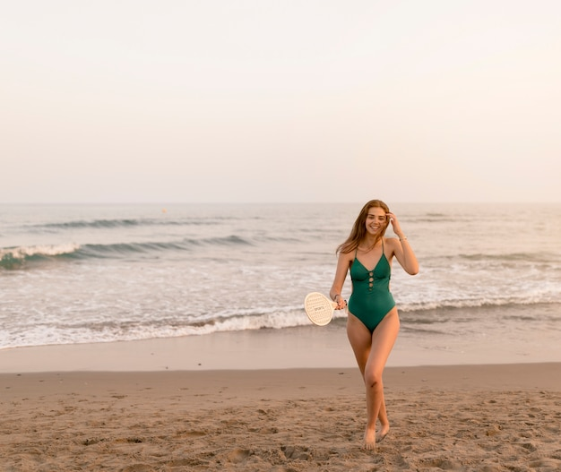 Adolescente souriante en bikini vert tenant la raquette debout près du bord de la mer