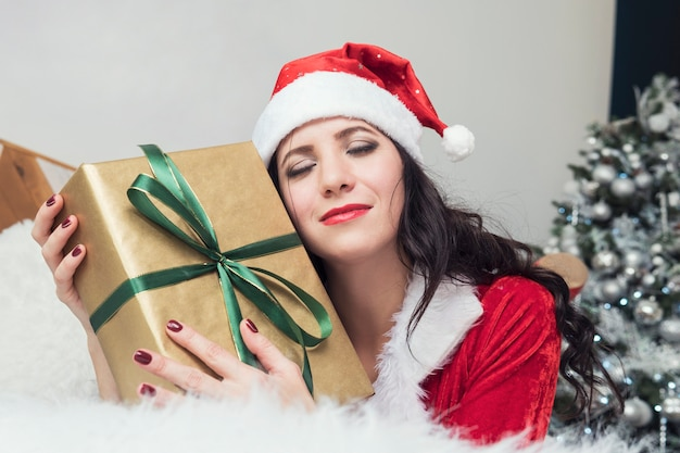 Adolescente souriante en bonnet de noel avec de nombreux coffrets cadeaux sur fond blanc. fille de santa émotionnelle positive. concept de vente et achats de noël. noël. fille étreignant des cadeaux.