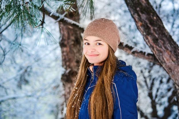Adolescente souriante dans une doudoune bleue et un chapeau brun sur fond d'hiver de branches de sapin enneigé