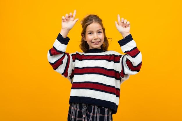 Adolescente souriante dans un pull décontracté à rayures montre sur le mur avec copie espace