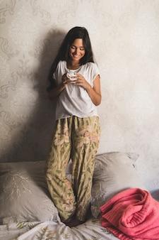 Adolescente souriante, debout sur le lit, tenant une tasse de café