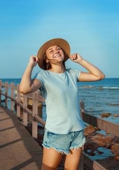 Une adolescente souriante debout sur une passerelle en bois au bord de la mer au coucher du soleil, portant un t-shirt bleu clair et touchant des deux mains son chapeau de paille. concept de voyage d'été
