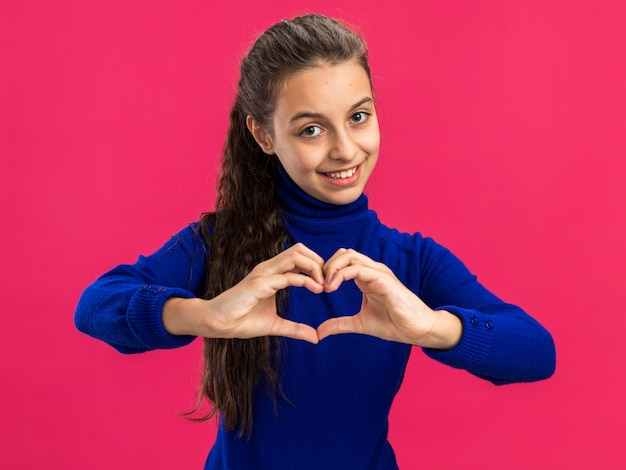 Adolescente souriante faisant un signe de coeur regardant devant faisant un signe de coeur isolé sur un mur rose