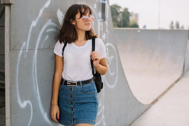 Adolescente souriante à lunettes et bretelles debout contre un mur dans une rue.