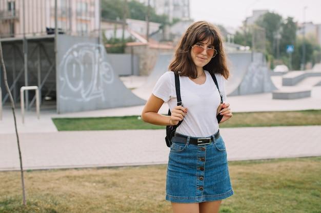 Adolescente souriante à lunettes et bretelles tout seul contre une rue.