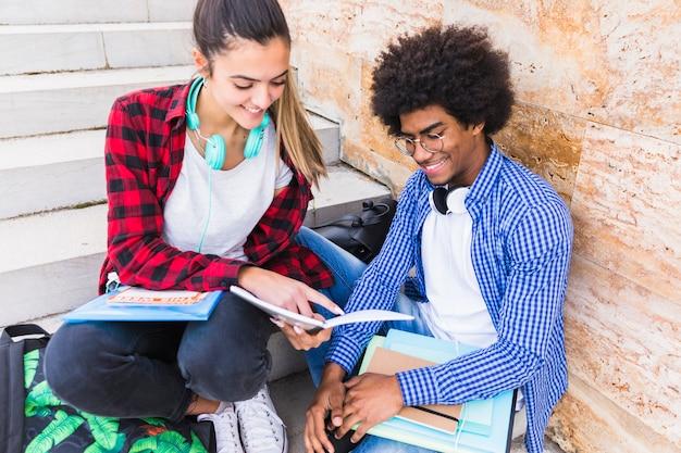 Adolescente souriante montrant quelque chose sur un livre à son amie