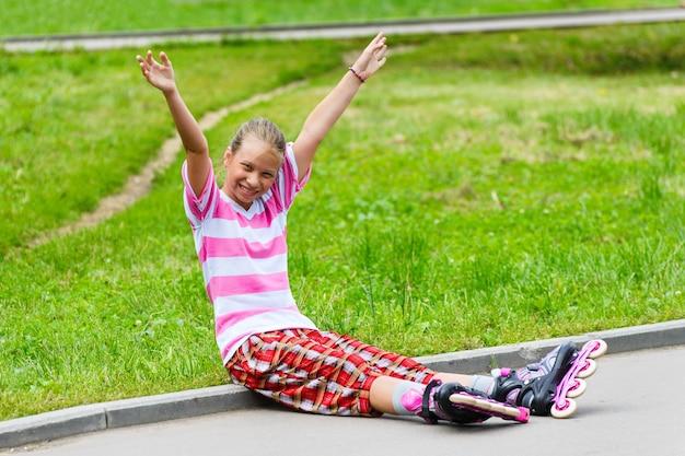 Une adolescente souriante en patins à roulettes assis sur le chemin asphalté. il agite les bras en guise de salutation. journée ensoleillée.