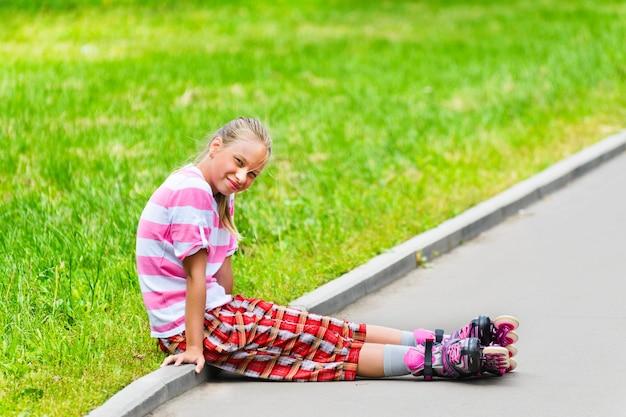 Une adolescente souriante en patins à roulettes assis sur le chemin asphalté.