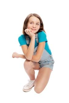 Adolescente souriante en salopette en jean s'accroupit. isolé sur fond blanc