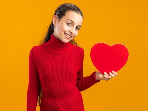 Adolescente souriante tenant en forme de coeur regardant devant isolé sur mur orange
