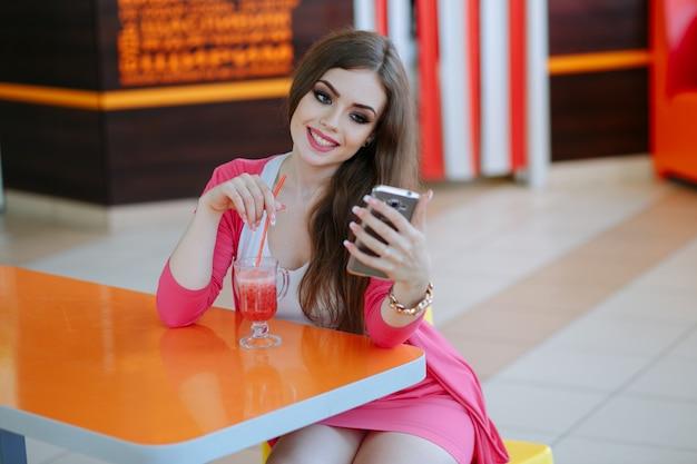 Une adolescente souriante tout en prenant une photo d'auto