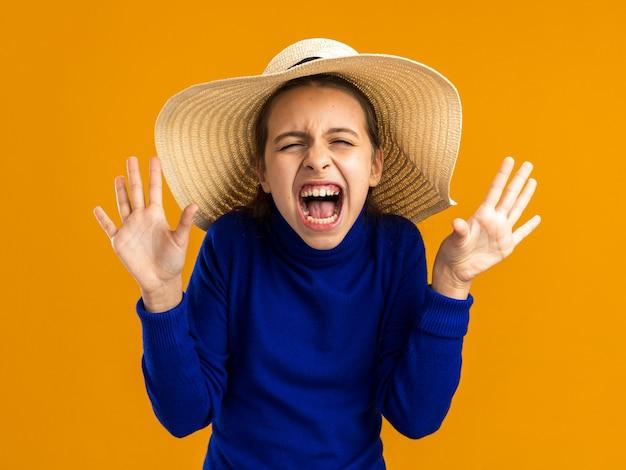 Adolescente stressée portant un chapeau de plage montrant des mains vides criant isolées sur un mur orange