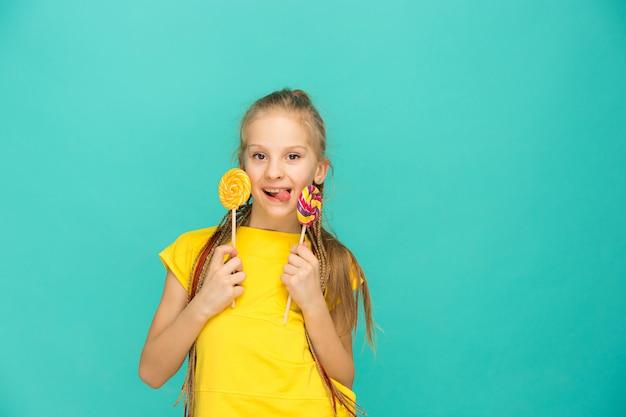L'adolescente avec sucette colorée sur un mur bleu