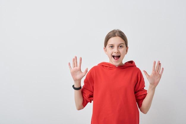 Adolescente sympathique et joyeuse en sweat-shirt rouge vous regarde avec ses paumes ouvertes et exprimant la joie sur fond blanc