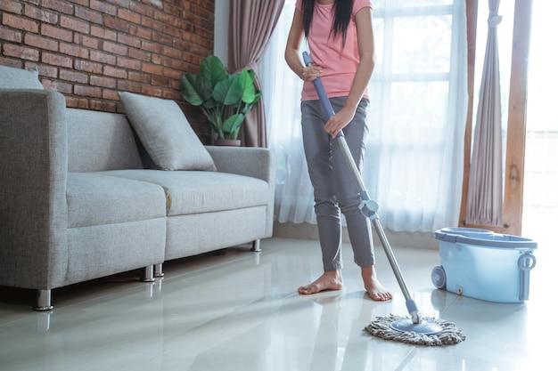 Adolescente tenant un bâton de vadrouille faire des tâches ménagères