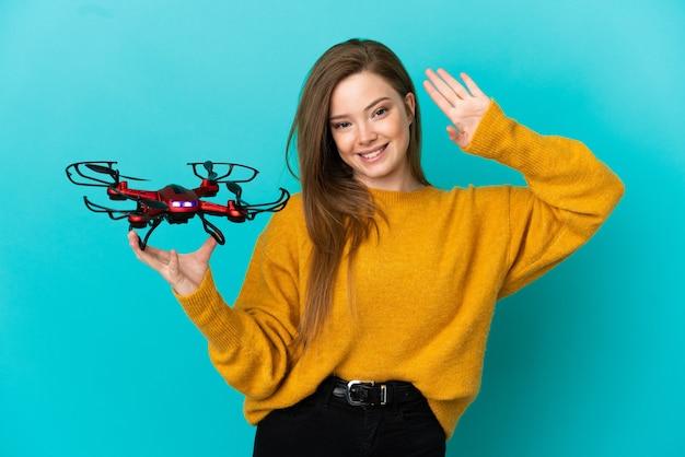 Adolescente tenant un drone sur fond bleu isolé saluant avec la main avec une expression heureuse