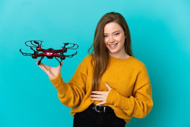 Adolescente tenant un drone sur fond bleu isolé souriant beaucoup