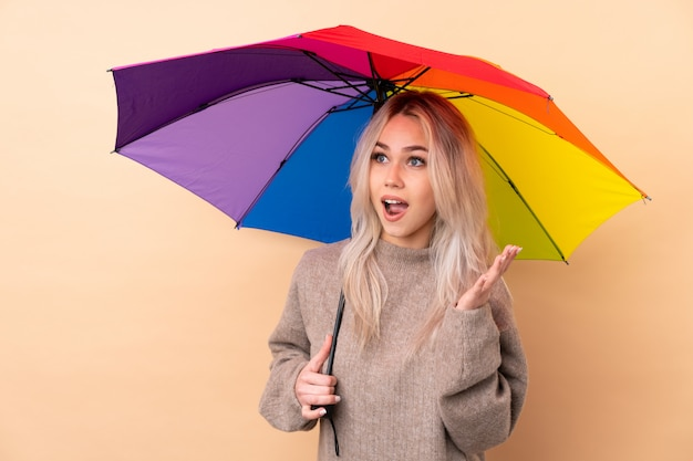 Adolescente tenant un parapluie sur le mur avec une expression faciale surprise