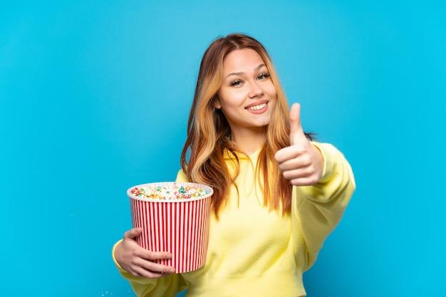 Adolescente tenant des pop-corn sur fond bleu isolé avec les pouces vers le haut parce que quelque chose de bien s'est passé