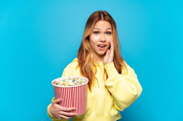Adolescente tenant des pop-corns sur fond bleu isolé avec une expression faciale surprise et choquée