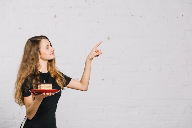 Adolescente tenant une tranche de gâteau avec une bougie en pointant son doigt sur quelque chose