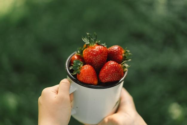 Une adolescente tient une fraise mûre et savoureuse dans une tasse d'aliments vitaminés d'été.