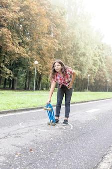 Une adolescente tient une planche à roulettes dans ses mains et attend avec impatience