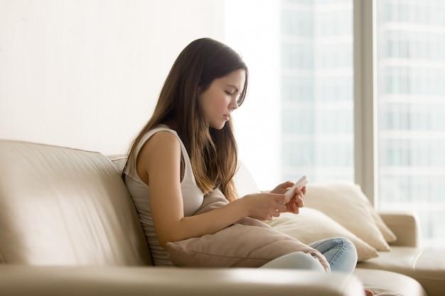 Adolescente triste à l'aide de téléphone assis sur un canapé
