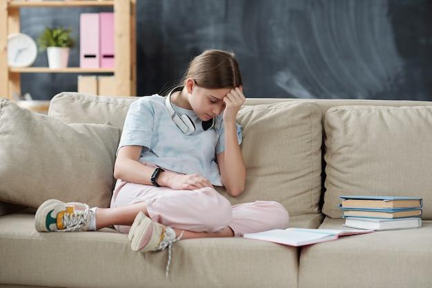 Adolescente triste étant bouleversée à cause de l'isolement à la maison alors qu'il était assis sur un canapé avec un livre ouvert et étudie la littérature