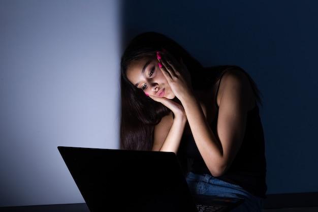 Adolescente triste et féminine avec tablette et ordinateur portable souffrant d'une cyberintimidation