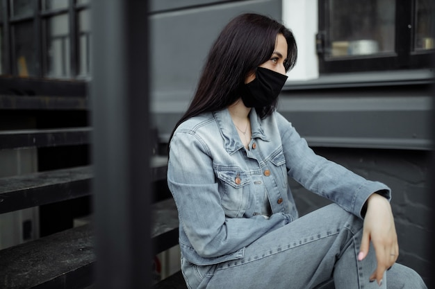 Adolescente triste en masque médical derrière les barreaux. les écoles sont mises en quarantaine en raison de maladies, d'épidémies. pandémie de coronavirus. covid 19.