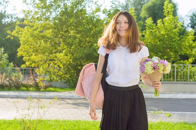 Adolescente va le premier jour à l'école, avec sac à dos, fleurs