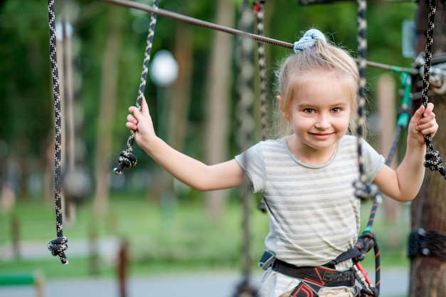 Adolescente va sur le sentier articulé dans le parc de corde.