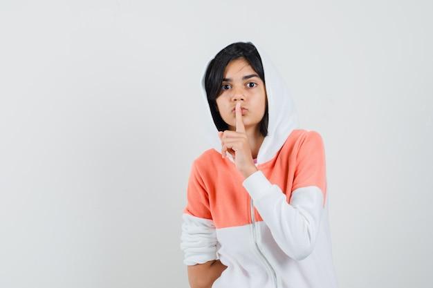 Adolescente en veste montrant le geste de silence et à la recherche de silence.